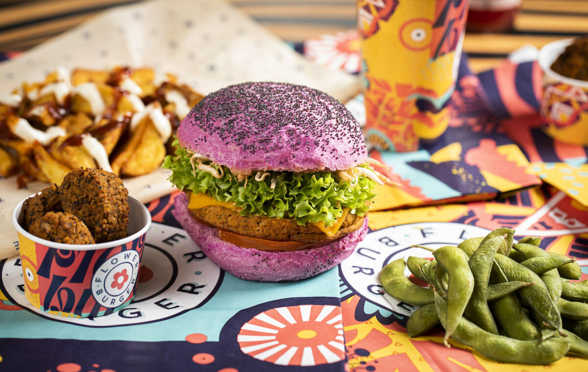 The Cherry Bomb Flower Burger with a vibrant pink bun filled with a lentil patty, lettuce, tomato confit, soybean sprouts, flower cheddar and rocktail sauce (Photo Credit: John Carey)