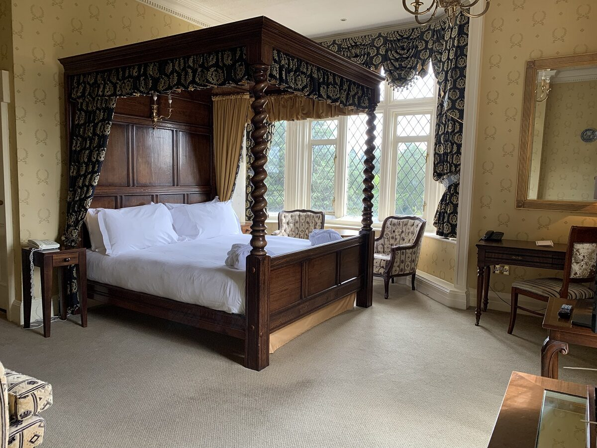 A four poster bedroom in the original Crewe Hall building features traditional antique furniture